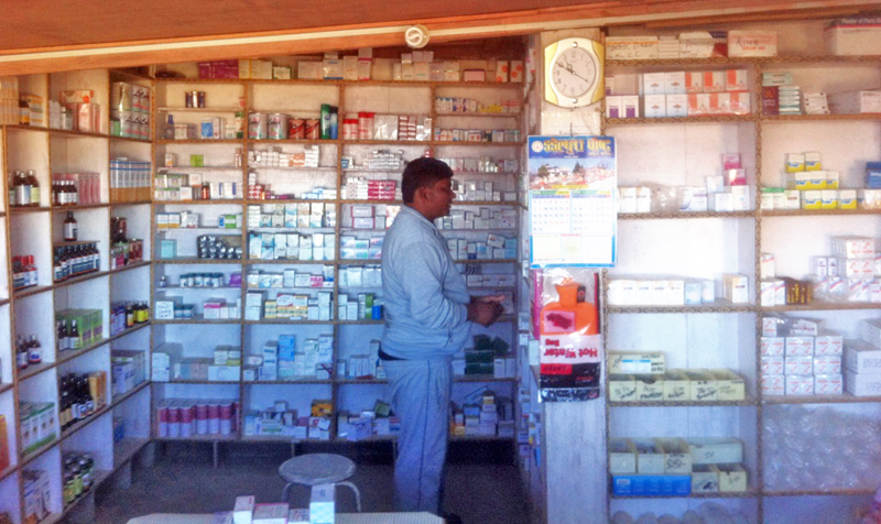 A drug store owner observing the available medicines, in Sajha Drug Store, in Dadeldhura Sub-regional Hospital, on Thursday, December 24, 2015. Photo: ThT
