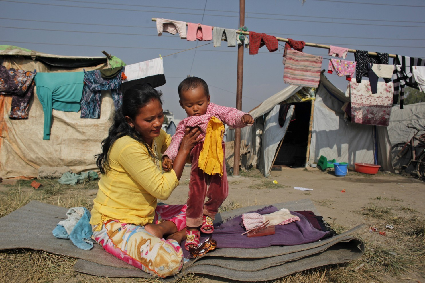 Anjana Shrestha, 28, holds her 19-month-old daughter Smriti at a temporary shelter at the Chuchhepati Camp, where she has been living since the earthquake in April, in Kathmandu, Nepal, Tuesday, December 1, 2015.