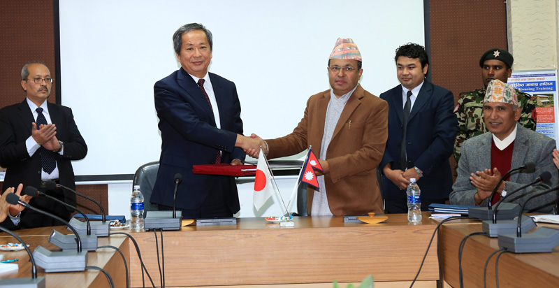 Finance Secretary Lok Darshan Regmi (right) and Japanese Ambassador to Nepal Masashi Ogawa exhange the Nepal-Japan agreement to provide Japanese Yen 30 billion (approximately Rs 26 billion) loan for Nepal's earthquake recovery programmes, at a function organised at the Ministry of Finance in Kathmandu, on Monday, December 21, 2015. Photo: JICA