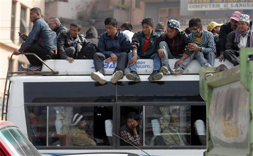 In this Nov. 27, 2015 photo, Nepalese people sit on the top of a crowded public bus in Kathmandu, Nepal. An ethnic groupu0092s blockade of a key border point with India is leaving Nepal with only about 15 percent of its normal supply of gasoline, diesel and cooking fuel, and creating shortages of other goods including food and medicine. (AP Photo/Niranjan Shrestha)