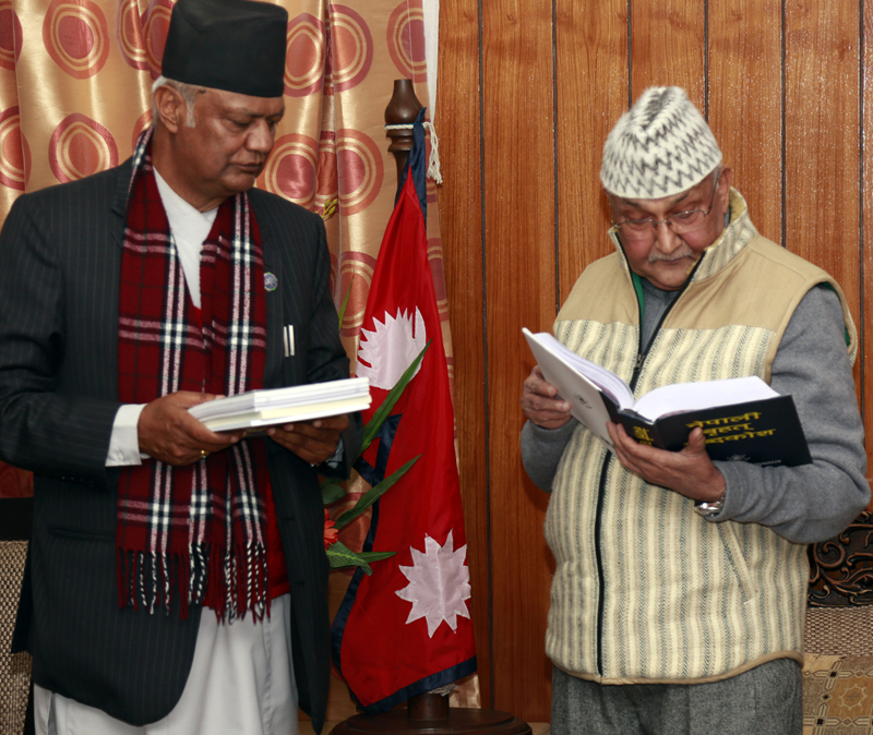 Prime Minister KP Sharma Oli looks at a dictionary as Nepal Academy Chancellor Ganga Prasad Uprety (right) gifts him the book, in Kathmandu, on Sunday, December 13, 2015. Photo: RSS