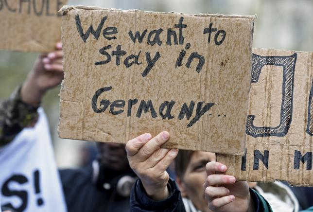 People hold signs during a pro-refugee demonstration in downtown Hamburg, Germany November 14, 2015.  REUTERS/Fabian Bimmer