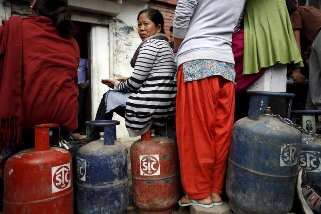 A woman sits on top of their empty cooking gas cylinders while waiting in a queue to buy cooking gas during the ongoing fuel crises that has been continuing for over a month now in Kathmandu, Nepal October 30, 2015. REUTERS/Navesh Chitrakar
