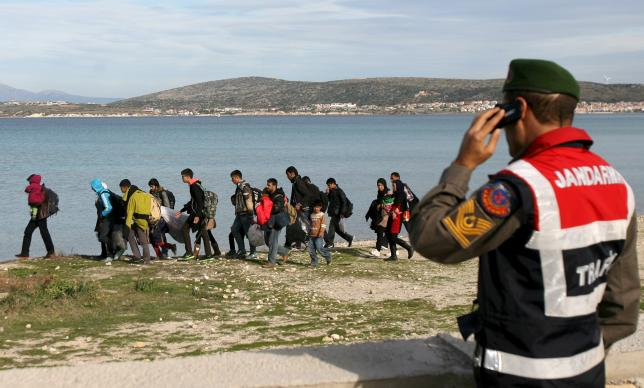 A Turkish Gendarme leads a group of refugees to buses to prevent them from sailing off for the Greek island of Chios in dinghies, at a beach in the western Turkish coastal town of Cesme, in Izmir province, Turkey, December 1, 2015. REUTERS/Denizhan Guzel