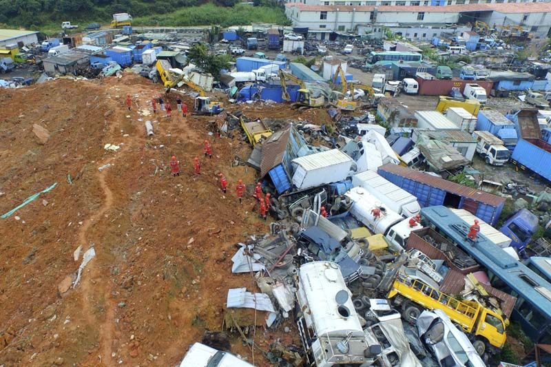 An aerial view shows rescuers walk among damaged vehicles to search for survivors at the site of a landslide which hit an industrial park in Shenzhen, Guangdong province of China, on Sunday, December 22, 2015. Photo: Reuters