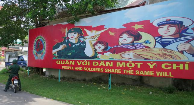 A soldier stands parks his motorcycle in front of a banner at the headquarters of the Division 308 special military force in Xuan Mai town, outside Hanoi July 10, 2015.      Photo: REUTERS