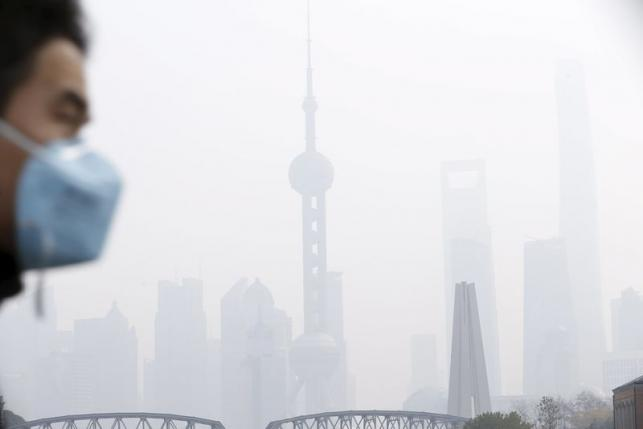 A man wearing a face mask walks on a bridge in front of the financial district of Pudong amid heavy smog in Shanghai, China, December 15, 2015. Photo: REUTERS