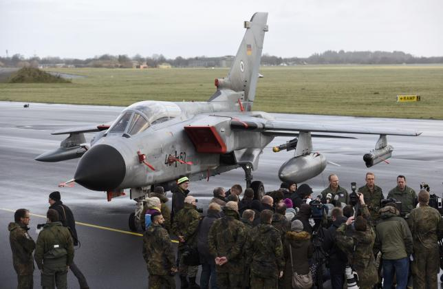 Journalists stand in front of a Tornado aircraft of the Tactical Air Force Wing 51 'Immelmann' during a presentation at German army Bundeswehr airbase in Jagel near the German-Danish border, December 4, 2015. REUTERS/Fabian Bimmer