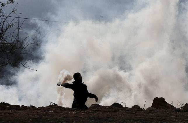A Palestinian protester returns a tear gas canister fired by Israeli troops during clashes in the West Bank village of Silwad, near Ramallah, December 11, 2015. Photo: REUTERS