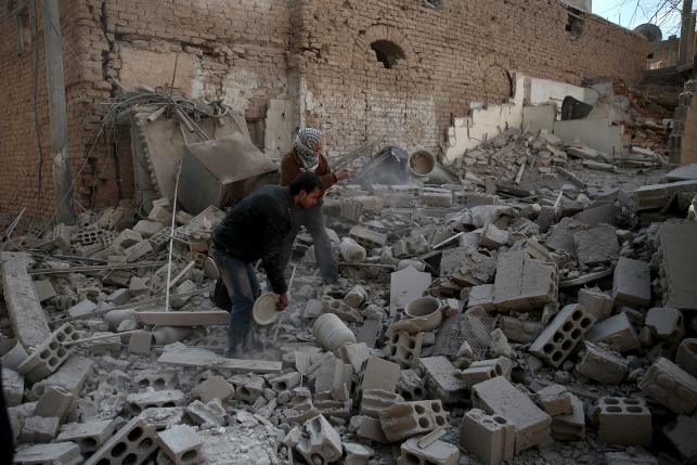 Men search for belongings at a site hit by missiles in the Douma neighborhood of Damascus, Syria December 13, 2015. Photo: REUTERS