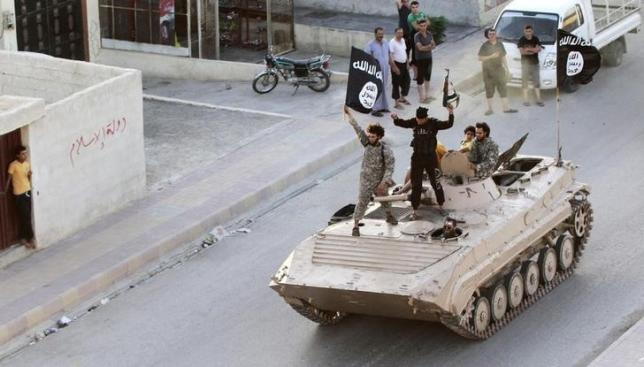 Militant Islamist fighters hold the flag of Islamic State (IS) while taking part in a military parade along the streets of northern Raqqa province in this June 30, 2014 file photo.  Photo; Reuters