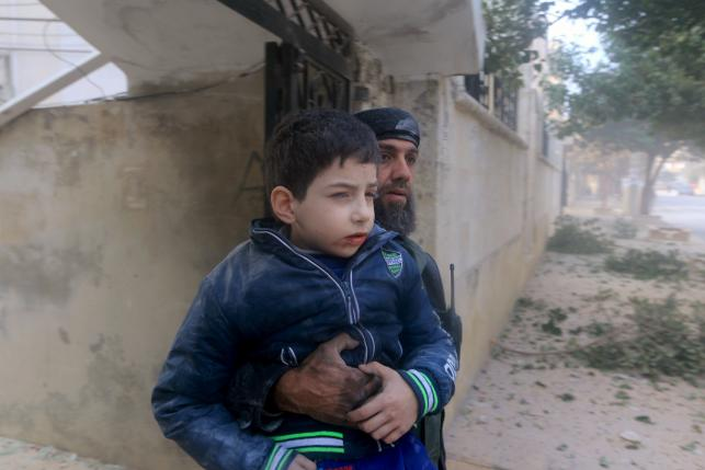 A rescue worker holds an injured boy after what activists said were airstrikes carried out by the Russian air force in Idlib city, Syria December 20, 2015. Photo: Reuters