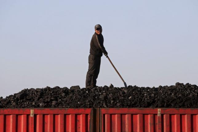 A worker speaks as he loads coal on a truck at a depot near a coal mine from the state-owned Longmay Group on the outskirts of Jixi, in Heilongjiang province, China, October 24, 2015. Photo: REUTERS