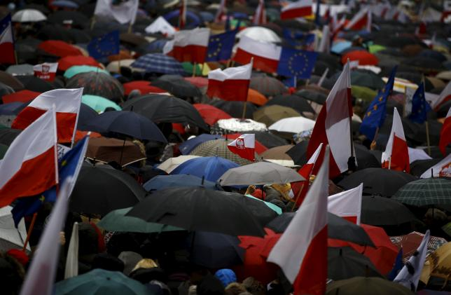 People holding European Union (EU), Polish national flags and umbrellas take part in an anti-government demonstration in front of the Constitutional Court in Warsaw, Poland December 12, 2015. Photo: REUTERS