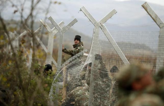 Macedonian soldiers erect a metal fence on the border with Greece, near Gevgelija, Macedonia, November 28, 2015.  REUTERS/Stoyan Nenov