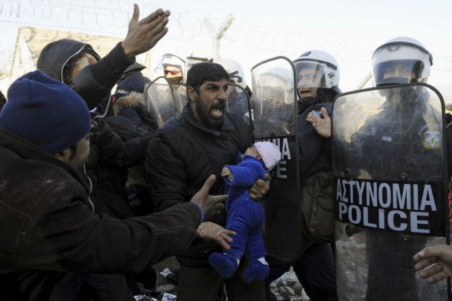 A stranded migrant holding a baby shouts next to a Greek police cordon following scuffles at the Greek-Macedonian border, near the village of Idomeni, Greece, December 3, 2015. Photo: Reuters