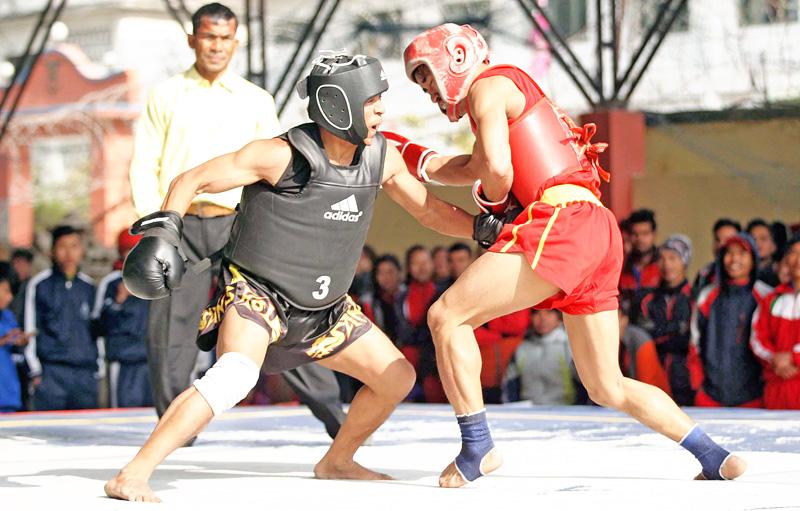 Raj Kumar Rasaili (left) of Bhaktapur fights against Ashok Khaling of Nepal APF Club during their menu2019s 52kg final bout of the 12th South Asian Games Wushu Selection Tournament in Kathmandu on Monday. Photo: THT
