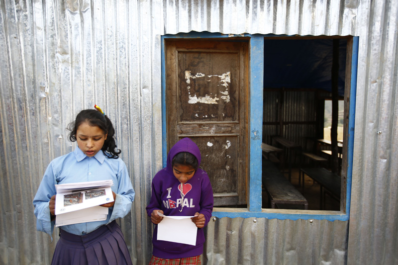 Two girls read pages on building strong houses in front of their makeshift class during an awareness program in Bhotechaur, Sindhupalchok on Thursday, January 14, 2016. Photo: THT