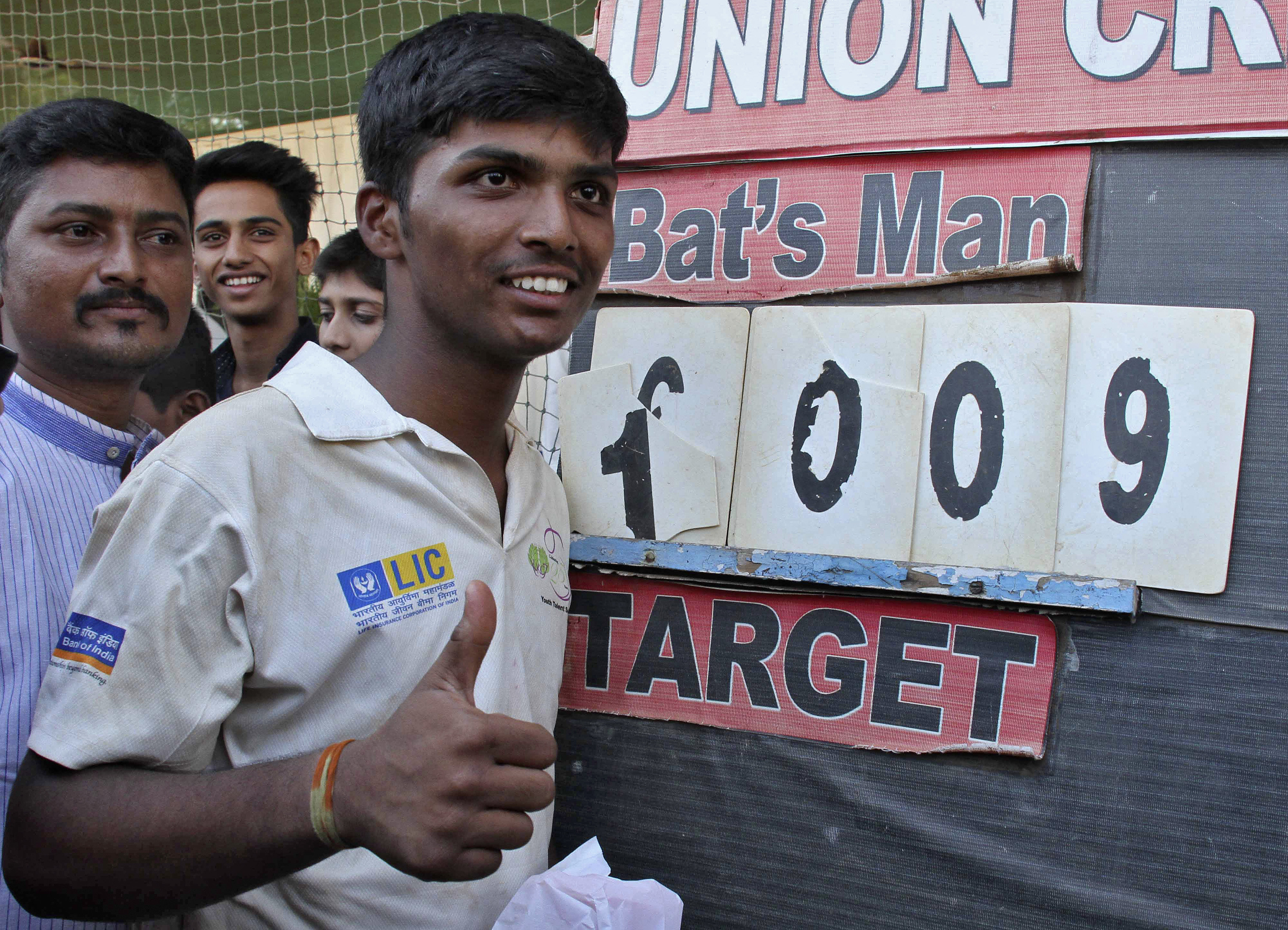 Schoolboy Pranav Dhanawade, 15, gestures as he poses next to the scoreboard during an inter-school cricket tournament in Mumbai, India, January 5, 2016. Photo: Reuters
