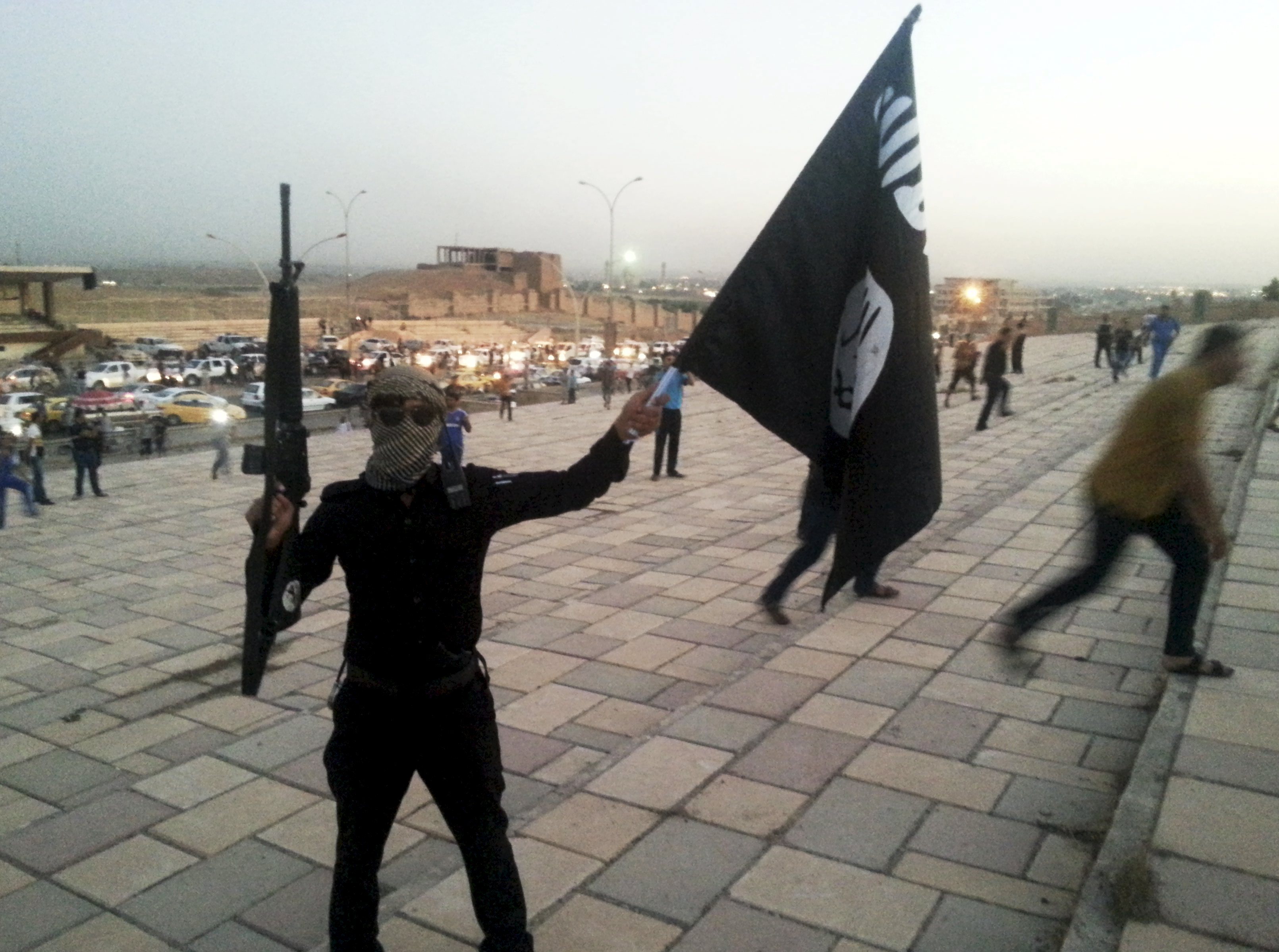 A fighter of the Islamic State of Iraq and the Levant (ISIL) holds an ISIL flag and a weapon on a street in the city of Mosul, Iraq, in this June 23, 2014 file photo. Photo: AP