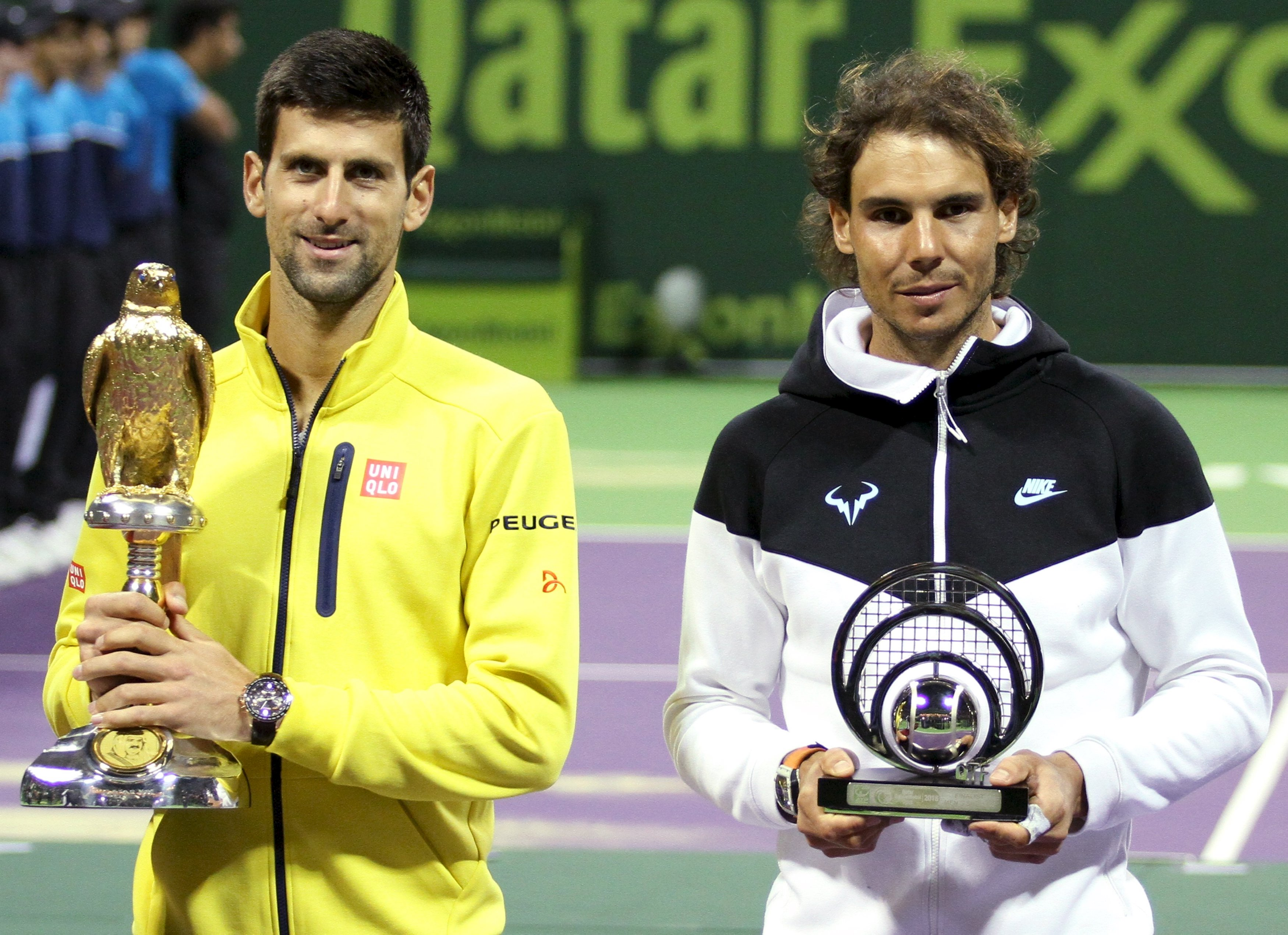 Novak Djokovic (left) of Serbia holds the trophy as he stands next to second place Rafael Nadal of Spain after winning his Qatar Open men's single tennis final match in Doha, Qatar, January 9, 2016. Photo: Reuters