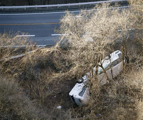 A bus lies after it veered off to the opposite lane on a mountain road in Karuizawa, Nagano prefecture, central Japan Friday, Jan. 15, 2016. Rescue officials say the overnight tour bus on its way to a ski resort in central Japan slid down the mountainside, killing at least more than a dozen passengers. Photo: AP