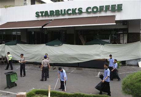 Workers clean up outside the Starbucks cafe where an attack occurred on Thursday, in Jakarta, Indonesia, Friday, Jan. 15, 2016. Indonesians were shaken but refusing to be cowed a day after a deadly attack in a busy district of central Jakarta that has been claimed by the Islamic State group. Photo: AP