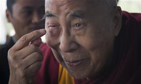 Tibetan spiritual leader the Dalai Lama points to his swollen right eye as he talks to journalists before boarding his chartered flight in Dharmsala, India, Tuesday, Jan. 19, 2016. The Tibetan leader said that he was going to the Mayo Clinic in Rochester, N.Y., for a regular medical checkup. Photo: AP