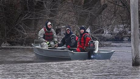Taylorville Fire Department Dive and Rescue Team members, from left, Jeff Stoner, Mike Mann and Nick Hackney search for two missing Christian County men, last seen Monday, while riding on a boat on the Sangamon River running through South Fork Township, Ill., Thursday, Dec. 31, 2015. Photo: Reuters