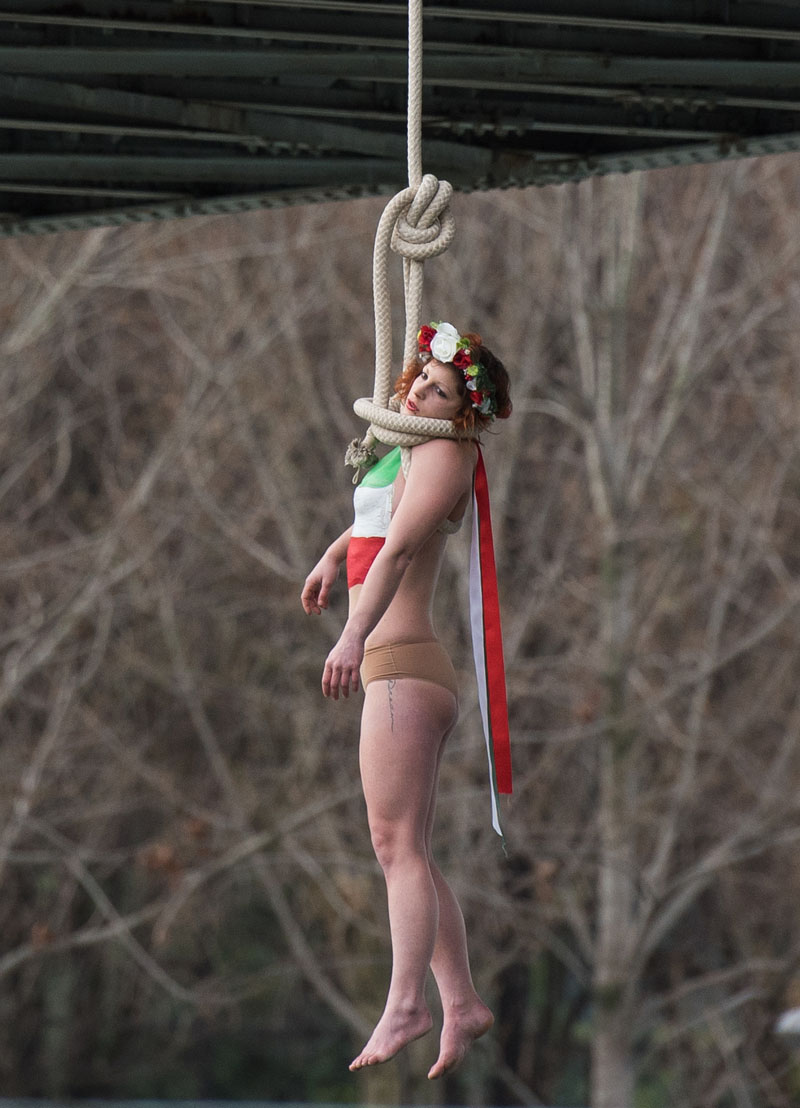 A Femen activist, Sarah Constantin, is hanged from a noose-like rope from a Paris bridge to call attention to the large number of executions in Iran as she stage a protest against visiting Iranian President Hassan Rouhani in Paris, on Thursday, January 28, 2016. A near-naked woman hanging from a noose-like rope from a Paris bridge has sent a message to visiting Iranian President Hassan Rouhani. Photo: AP