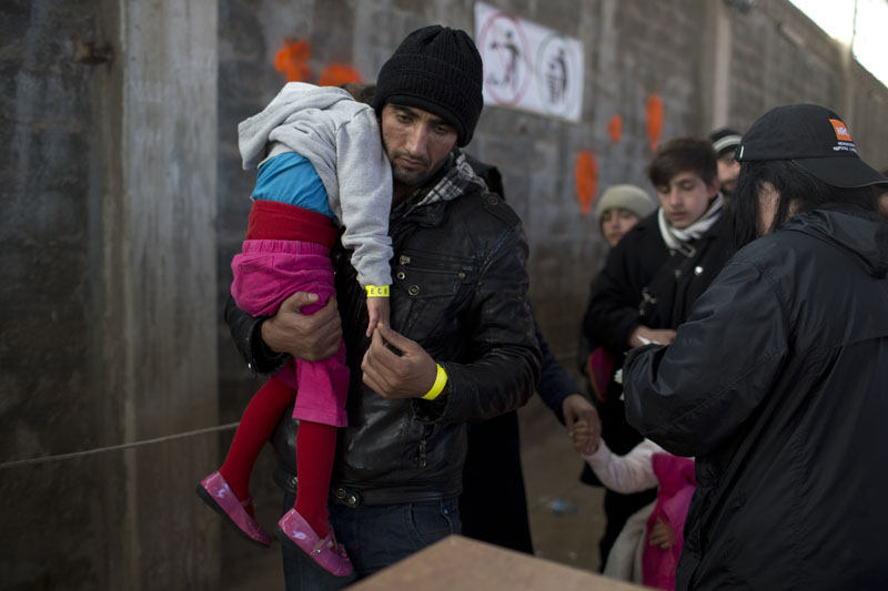 An Afghan man with his daughter walks after they receive a wristband tags at Tabakika registration center, Chios island, Greece, on Friday, January 15, 2016. Photo: AP