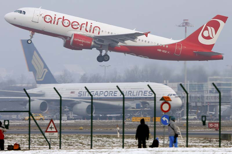 Plane spotters watch an Airbus A320-214 passenger jet of Air Berlin arline taking off from Zurich Airport, Switzerland on January 21, 2016. Photo: Reuters