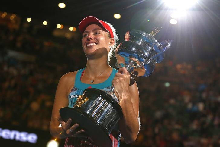 Germany's Angelique Kerber celebrates with the trophy after winning her final match against Serena Williams of the U.S. at the Australian Open tennis tournament at Melbourne Park, Australia, January 30, 2016. REUTERS/Thomas Peter