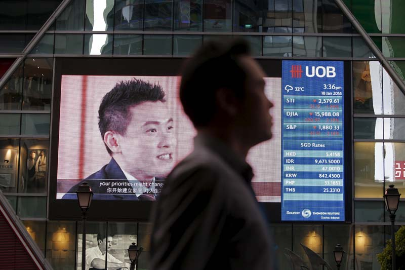 A man passes a board showing the decline of Straits Times Index (STI), Dow Jones Industrial Average (DJIA) and the Standard and Poor's (S&P) index at the central business district in Singapore, on January 18, 2016. Photo: Reuters