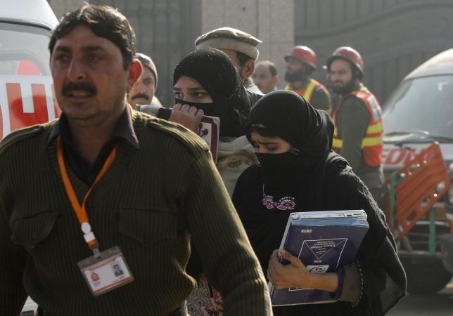 A rescue worker guides students, after they were rescued in a militant attack at Bacha Khan University, in Charsadda, Pakistan, January 20, 2016. REUTERS/Fayaz Aziz