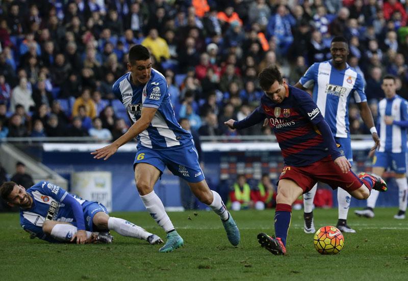 Barcelona's Lionel Messi (right) fights for the ball against Espanyol's Enzo Rocco during a Spanish La Liga soccer match at Cornella-El Prat stadium in Cornella Llobregat, Barcelona, Spain on  Saturday, January 2, 2016. Photo: AP