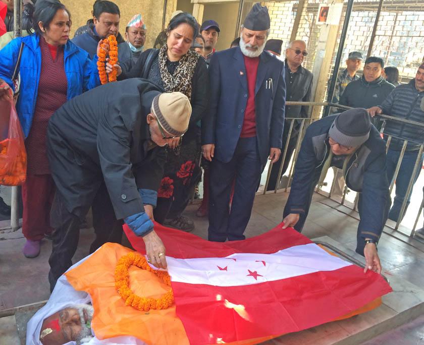 Nepali Congress President Sushil Koirala draping Nepali Congress party flag on late Birendra Dahal's body, in Kathmandu, on Sunday, January 17, 2016.