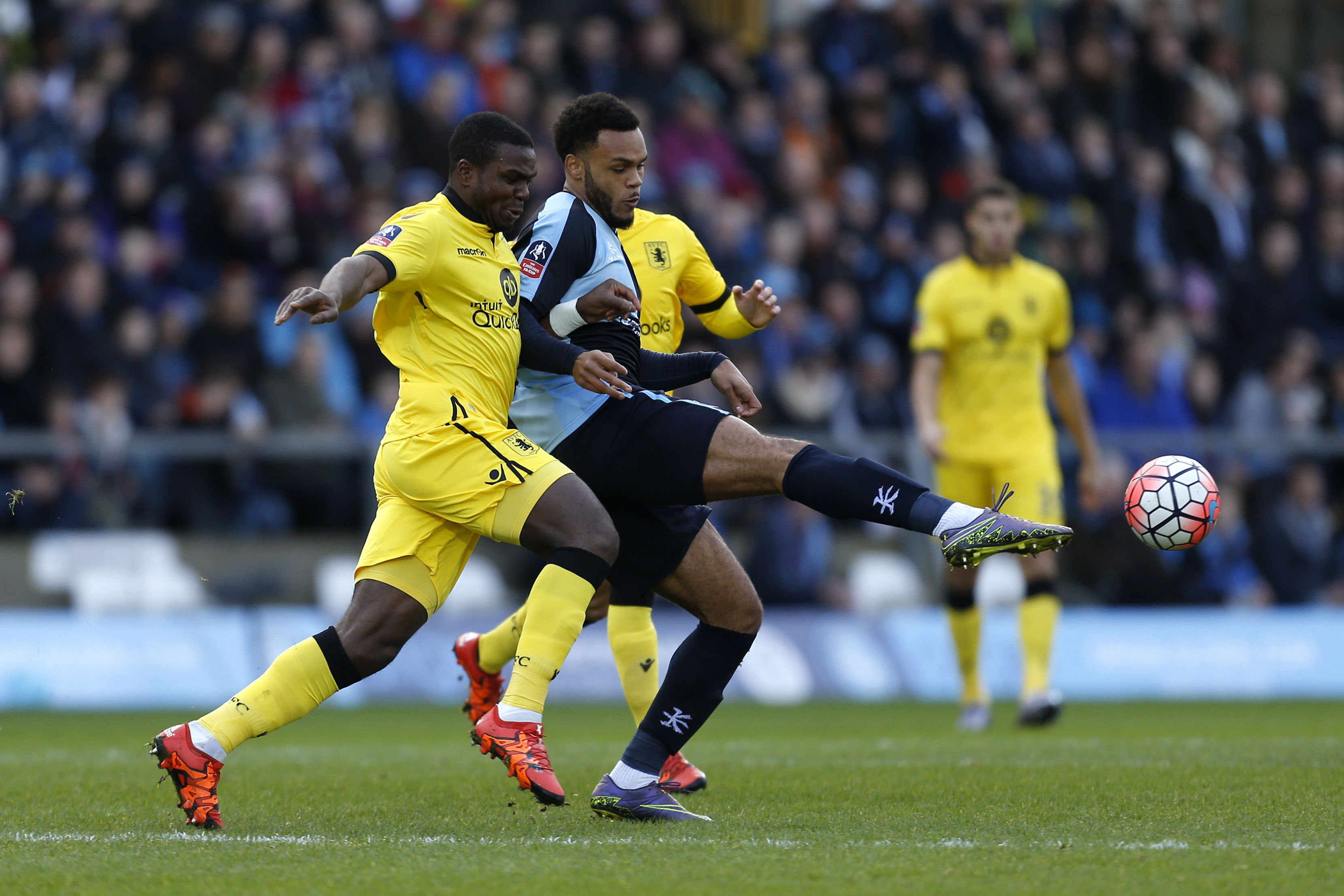 Wycombe Wanderers' Aaron Holloway, right, and Aston Villa's Jores Okore battle for the ball during their FA Cup, third round soccer match at Adams Park, High Wycombe, England, Saturday, January 9, 2016. Photo: AP