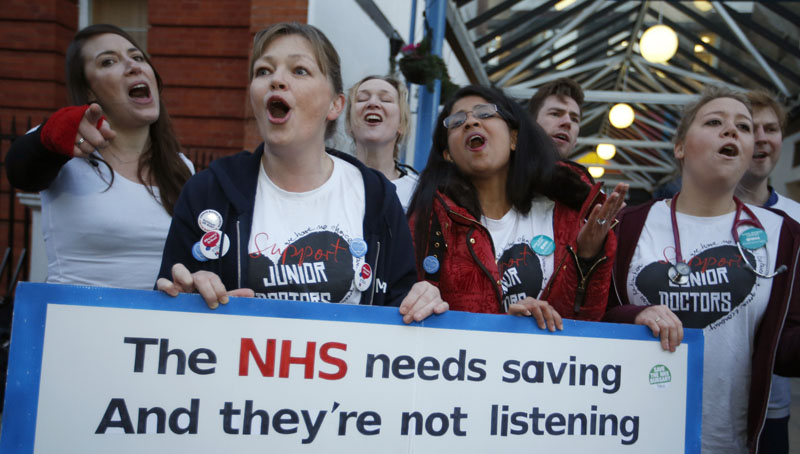 The British National Heath Service Singers, who are either doctors or nurses, perform a protest song in support of junior doctors outside Great Ormond Street Hospital for Sick Children, as a 24 hour junior doctor strike starts in London, Tuesday, January 12, 2016. Photo: AP