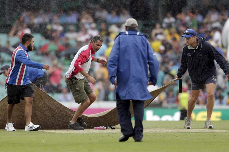 Groundskeepers rush to cover the wicket as rain hits the third cricket test between Australia and the West Indies at the SCG in Sydney, January 3, 2016. Photo: Reuters