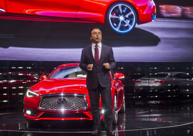 Carlos Ghosn, Chairman and CEO of Nissan Motors, talks about the new Infiniti Q60 sports coupe behind him on stage at the North American International Auto Show, Monday, January 11, 2016, in Detroit. Photo: AP