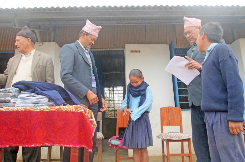 District Education Officer Top nBahadur Shrestha (left) distributing sweaters to Chepang students of Bhanu High School at Byas nMunicipality, Tanahun, on Sunday, January 17, 2016. Photo: THT