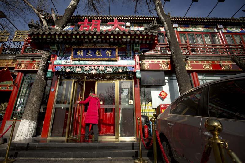A hostess walks through the door of a branch of the Hu Da hot pot restaurant chain in Beijing, on Friday, January 22, 2016. Photo: AP