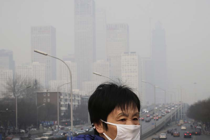 A woman wearing a mask for protection against pollution walks on a pedestrian overhead bridge as office buildings in Central Business District of Beijing are shrouded with smog, on December 20, 2015. Photo: AP/ File