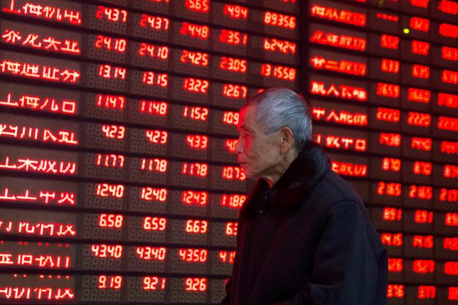 An investor walks past an electronic screen showing stock information at a brokerage house in Nanjing, Jiangsu province, January 19, 2016. REUTERS/China Daily