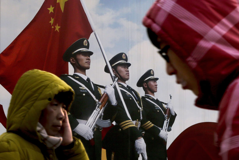People walk past a poster of Chinese People's Liberation Army (PLA) soldiers on display in Beijing, on Thursday, January 21, 2016. Photo: AP