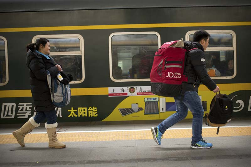 Passengers run to board a train at the Beijing Railway Station in Beijing, on Saturday, January 30, 2016. Photo: AP