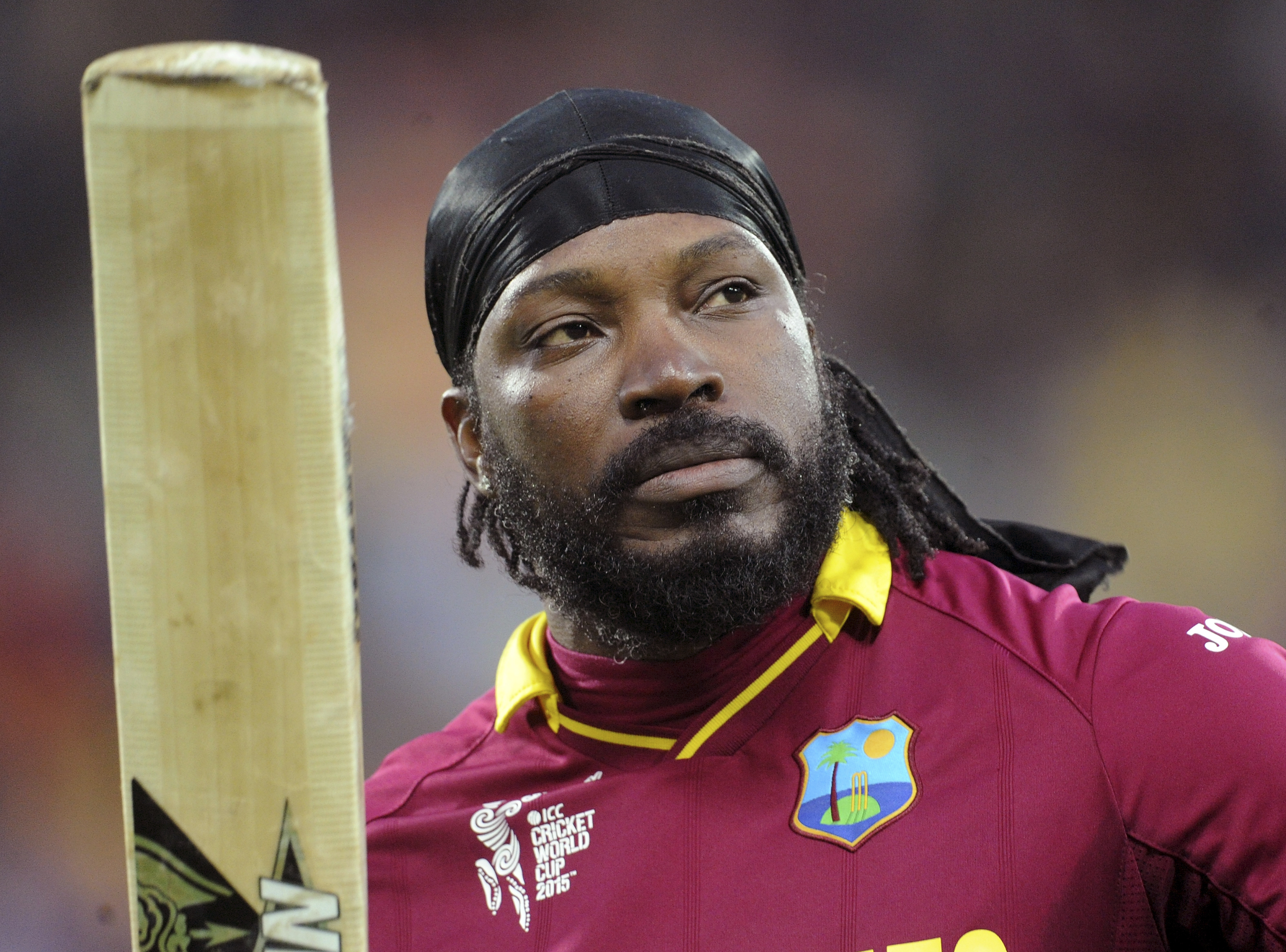 FILE - In this March 21, 2015 file photo, West Indies Chris Gayle waves his bat to the crowd as he leaves the field after he was dismissed for 61 runs while batting against New Zealand during their Cricket World Cup quarterfinal match in Wellington, New Zealand. Photo: AP