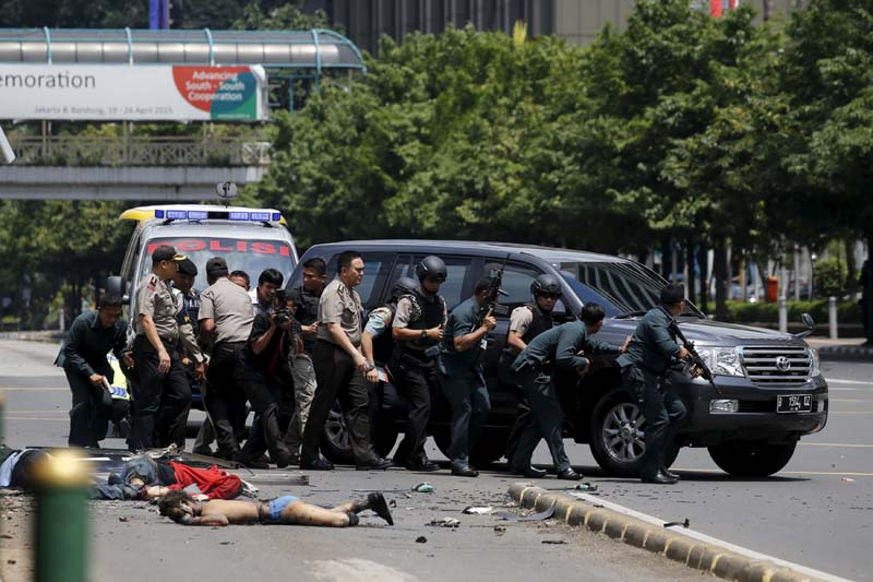 Dead bodies are seen as Indonesian police hold rifles while walking behind a car for protection in Jakarta January 14, 2016. Photo: Reuters