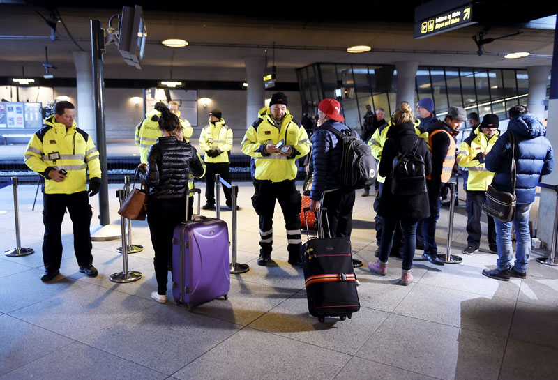 Security staff check IDs at Kastrups train station outside Copenhagen, Denmark on Monday, January  2015.  Sweden requires train companies with service across a bridge-and-tunnel link from Denmark to refuse passengers without IDs. Photo: AP
